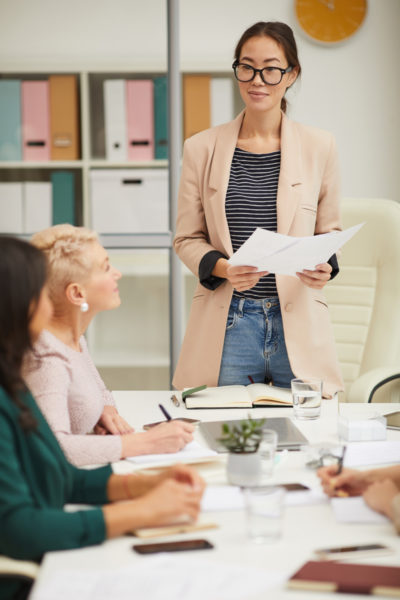 Beautiful Asian woman standing at table making presentation at business meeting vertical shot